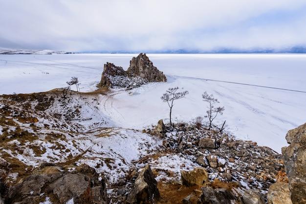 Cabo burhan na rocha de shamanka na ilha de olkhon no dia ensolarado de março. lago baikal com belas nuvens Foto Premium