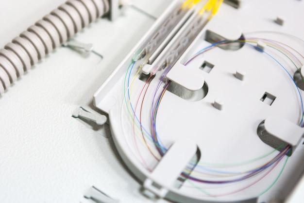 Cabo de fibra ótica do comunicate do trabalhador na caixa opto. instalando novo equipamento de rede Foto Premium