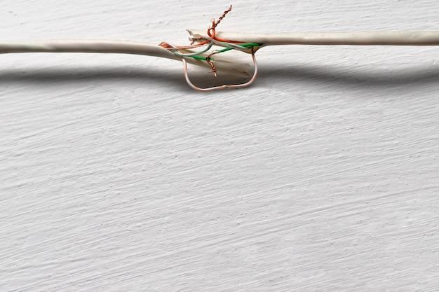 Cabo quebrado contra uma parede branca. os fios de cobre são torcidos à mão e não isolados. Foto Premium