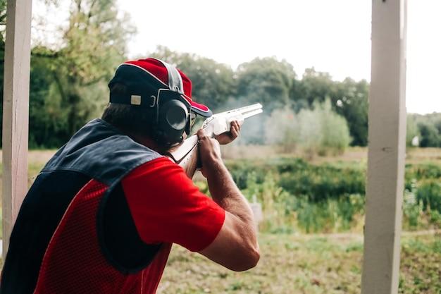 Caçador dispara com uma espingarda em um alvo em roupas especiais e fones de ouvido Foto gratuita