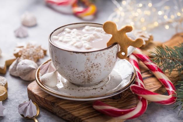 Cacau chocolate quente bebe com marshmallows em canecas de natal na superfície cinza. bebida quente tradicional, coquetel festivo no natal ou ano novo Foto Premium