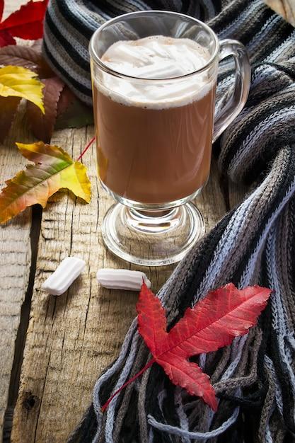 Cacau com marshmallows, cachecol e folhas de outono Foto Premium