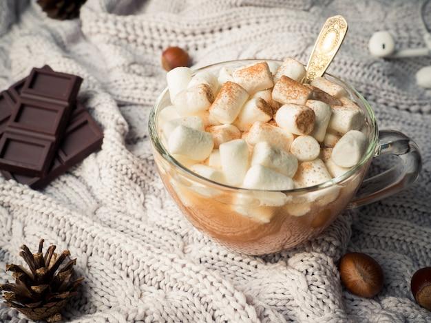 Cacau em uma xícara de vidro com um marshmallow, cones de chocolate com canela e nozes Foto Premium