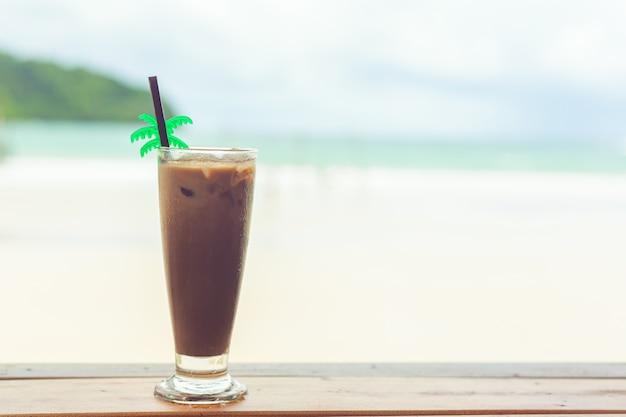 Cacau frio em um copo sobre uma mesa de madeira à beira-mar no verão Foto Premium