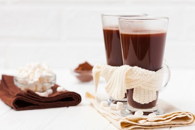Cacau quente em copos com marshmallow, decorações crocahet, guardanapos marrons e bege. Foto Premium