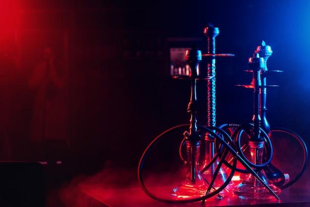 Cachimbo de água com brasas shisha em tigelas em um fundo de fumaça com iluminação neon em um restaurante com uma cópia Foto Premium