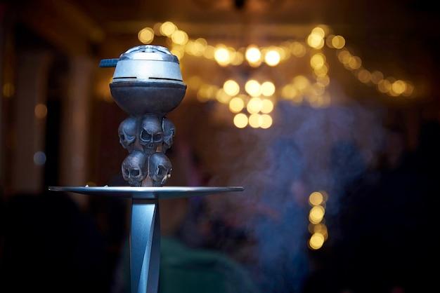 Cachimbo de água decorado com caveiras em uma nuvem de fumo close-up em um fundo desfocado Foto Premium