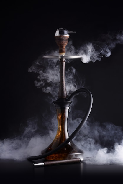 Cachimbo de água na moda com nuvem de fumaça em fundo preto Foto Premium