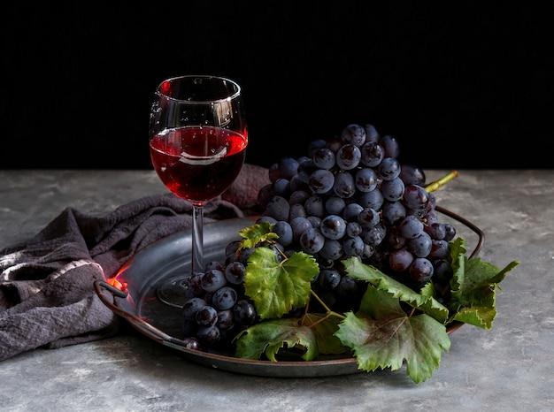 Cacho de uva escuro com água cai com pouca luz Foto Premium