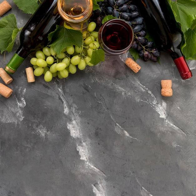 Cacho de uvas com garrafa de vinho no fundo de mármore Foto gratuita