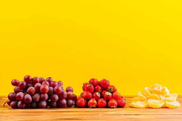 Cacho de uvas; morangos e fatia de laranja na mesa de madeira contra um fundo amarelo Foto gratuita