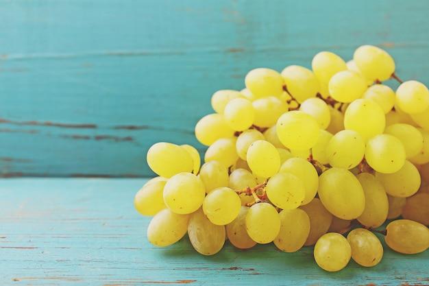 Cacho de uvas sobre um fundo azul Foto Premium