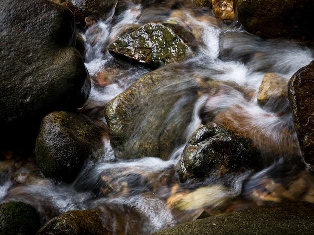Cachoeira da angra do córrego da montanha que corre através de rochas em uma floresta tropical. Foto Premium