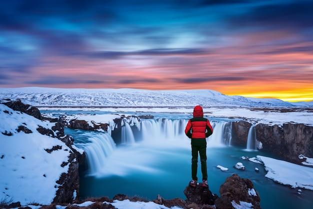 Cachoeira de godafoss ao pôr do sol no inverno, islândia. cara de jaqueta vermelha olha para a cachoeira godafoss. Foto gratuita
