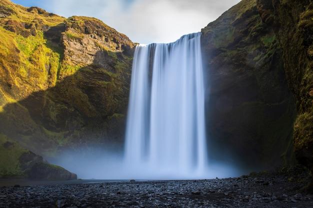 Cachoeira de skogafoss com arco-íris na islândia Foto Premium