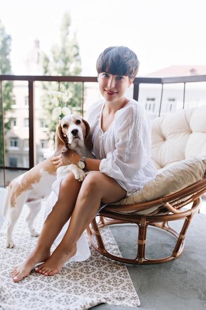 Cachorro beagle em pé sobre duas patas posando ao lado de uma garota morena atraente com pedicure branca relaxando no terraço Foto gratuita