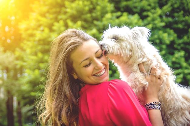 Cachorro branco cachorro lambendo é dono. garota atraente caucasiana se divertindo com seu cachorro Foto Premium