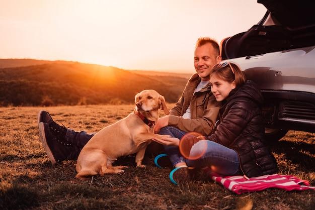 Cachorro dando pata para seus proprietários no acampamento na colina Foto Premium