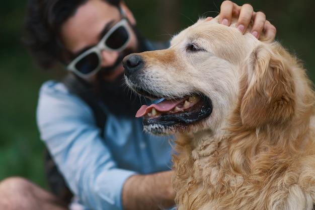 Cachorro e seu dono - cachorro legal e jovem se divertindo Foto gratuita