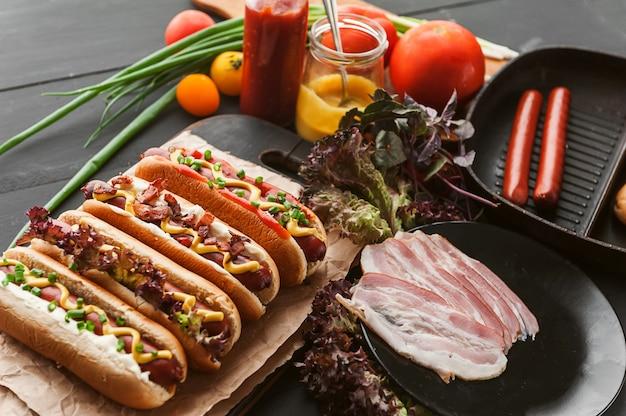 Cachorro-quente americano com ingredientes em um fundo escuro de madeira Foto Premium
