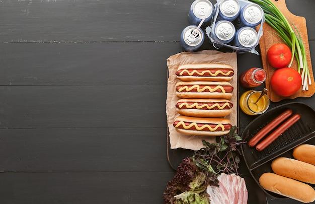 Cachorro-quente americano com ingredientes em uma superfície de madeira escura Foto Premium