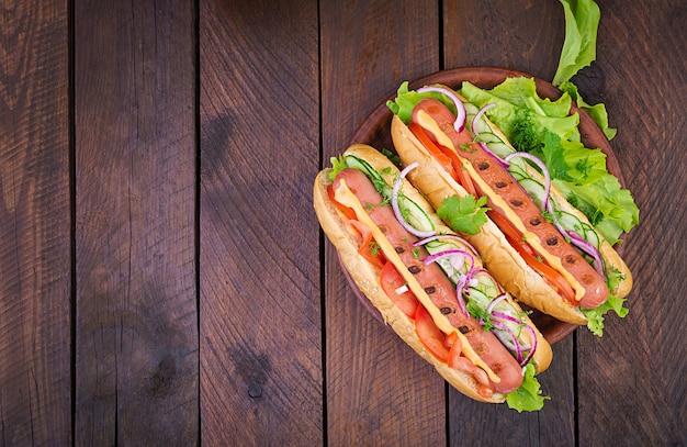 Cachorro-quente com salsicha, pepino, tomate e alface no fundo de madeira Foto Premium