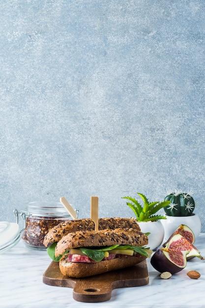 Cachorro-quente fresco na placa de madeira com frasco de flocos de pimenta; fatias de figo de planta em vaso e amêndoas Foto gratuita