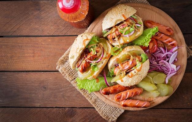 Cachorro-quente - sanduíche com picles, cebola vermelha e alface em fundo de madeira. vista do topo Foto Premium