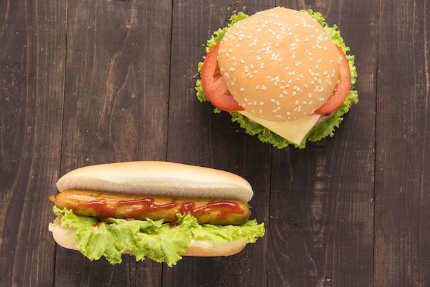 Cachorros-quentes e hambúrgueres na mesa de madeira Foto Premium