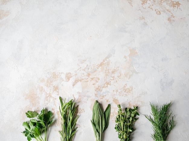 Cachos de ervas cruas frescas - alecrim, tomilho, endro, salsa e sálvia em um plano de fundo texturizado. vista do topo. Foto Premium