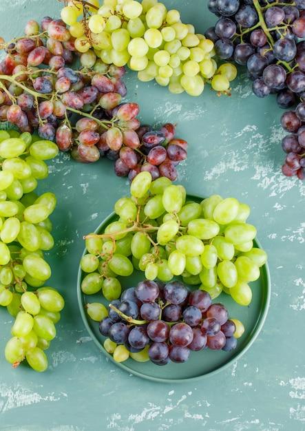 Cachos de uva em uma bandeja com fundo de gesso, vista superior. Foto gratuita