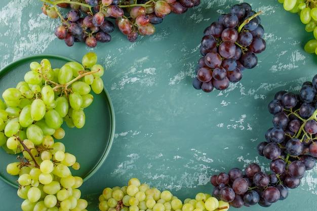 Cachos de uva em uma bandeja plana sobre um fundo de gesso Foto gratuita