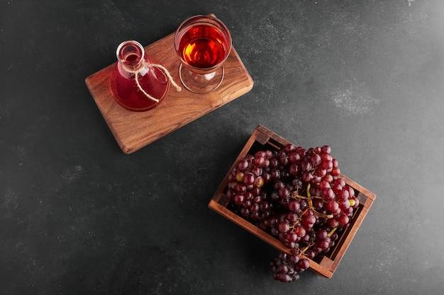 Cachos de uvas vermelhas em uma bandeja de madeira com uma taça de vinho, vista de cima. Foto gratuita
