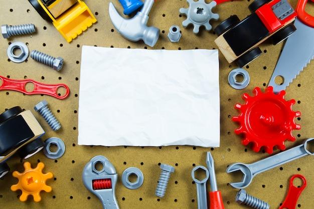 Caçoa ferramentas dos brinquedos da construção, ferramentas coloridas do brinquedo, construção no fundo de madeira. Foto Premium