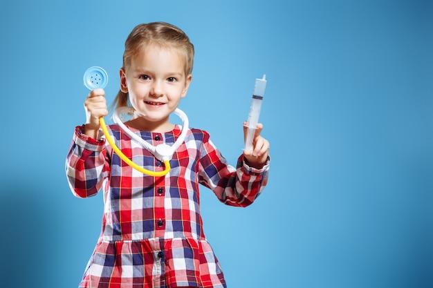 Caçoe a menina que joga o doutor com seringa e estetoscópio em um fundo azul. Foto Premium