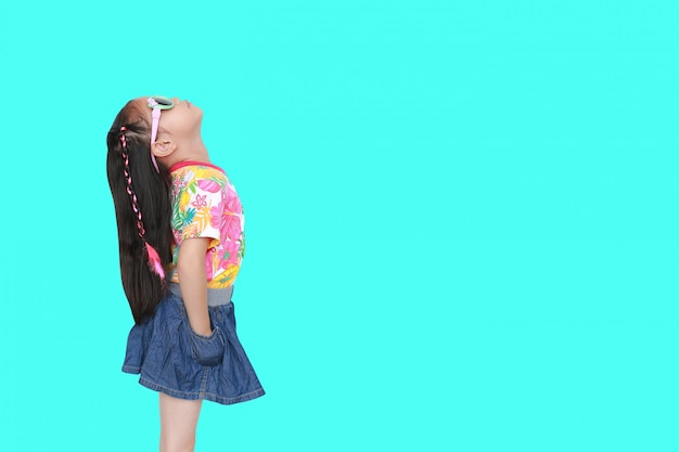 Caçoe a menina que veste um vestido e uns óculos de sol do verão das flores que olham isolados acima em ciano com espaço da cópia. Foto Premium