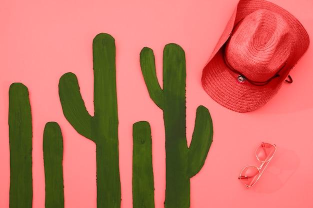 Cacto verde pintado com chapéu e óculos de sol no fundo coral Foto gratuita