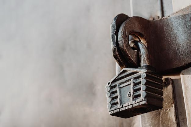 Cadeado na forma de uma cabana paira sobre as dobradiças do portão fechado. portões de metal. Foto Premium