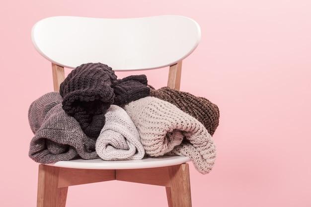 Cadeira branca com uma pilha de camisolas de malha em um fundo rosa Foto gratuita