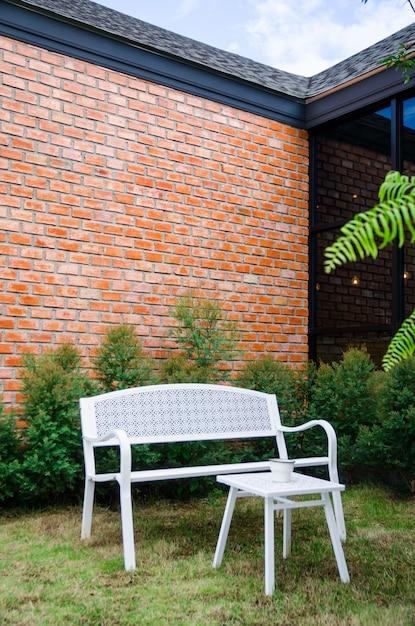Cadeira branca no jardim com fundo da parede de tijolo Foto Premium