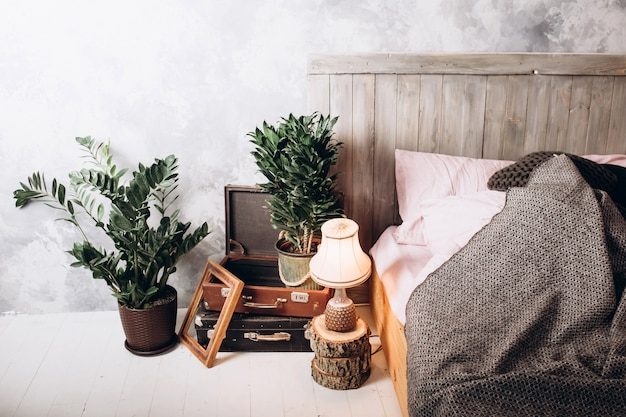Cadeira de madeira na penteadeira no interior do quarto pastel rosa com lâmpada de ouro ao lado da cama Foto Premium