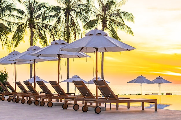 Cadeira de praia com guarda-chuva ao redor da piscina em hotel resort com praia de mar oceano e coqueiro ao pôr do sol Foto gratuita