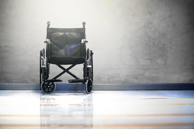Cadeira de roda no hospital no fundo cru do cimento com luz. Foto Premium