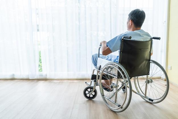 Cadeira de rodas paciente asiática no quarto vazio Foto Premium