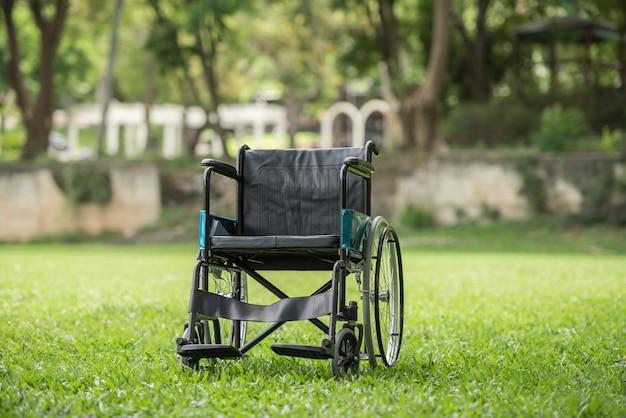 Cadeira de rodas vazia estacionada no parque, conceito dos cuidados médicos. Foto gratuita