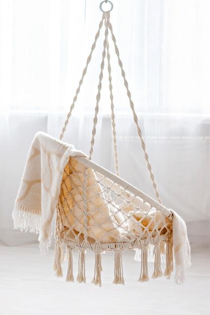 Cadeira de vime pendurada com manta bege em casa Foto Premium