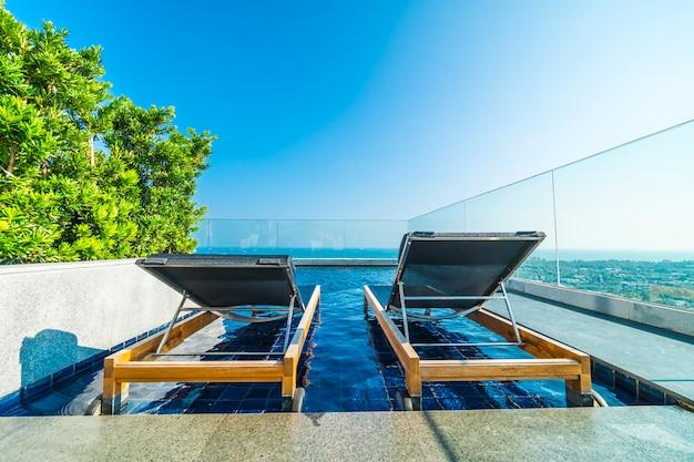 Cadeira e cama ao redor da piscina no hotel Foto gratuita
