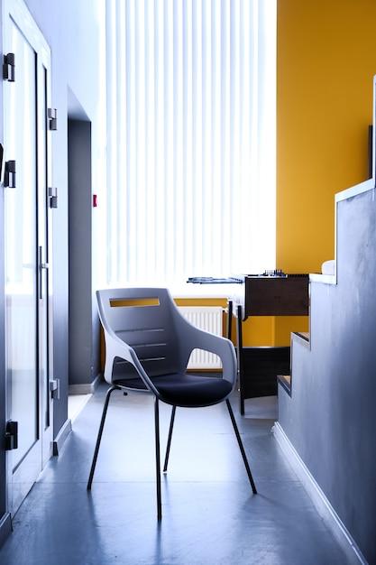 Cadeira preta no corredor do apartamento, foto real com espaço de cópia na parede branca Foto Premium