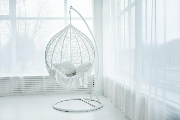 Cadeira suspensa no interior do quarto branco Foto Premium