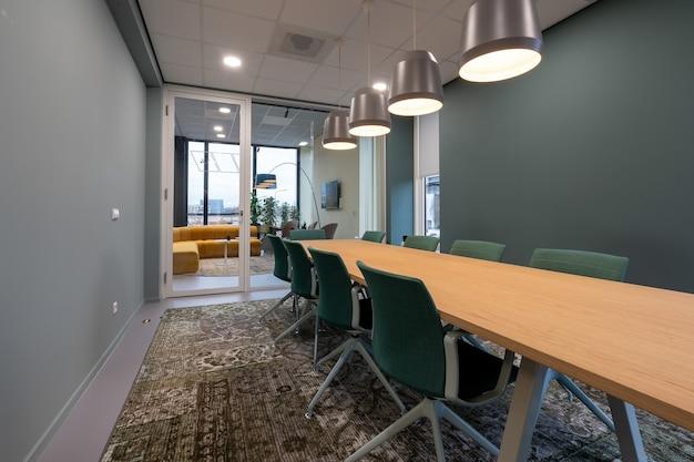 Cadeiras colocadas ao lado de uma mesa em uma sala com um tapete estampado Foto gratuita
